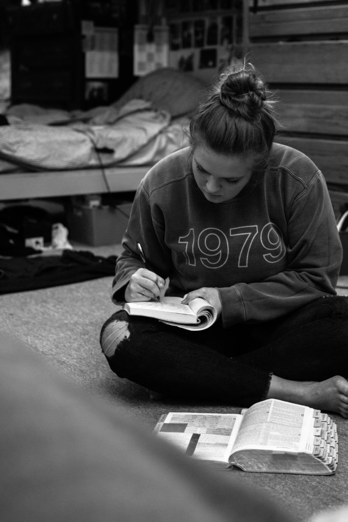 A DTS student reading her Bible and writing on her journal during one of her personal devotions