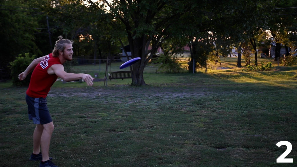 A student, Trenton, throwing a frisbee